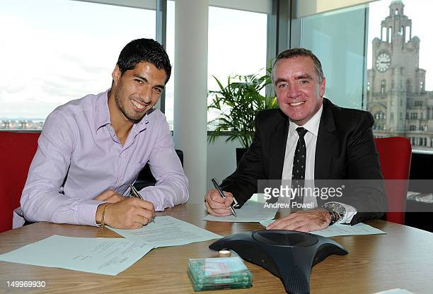 Luis Suarez signs a new contract with Liverpool FC next to Managing Director of Liverpool FC Ian Ayre at the LFC offices, Chapel St on August 7, 2012...