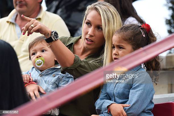 Luis Suarez's wife Sofia Balbi holds her son Benjamin Suarez as she talks with her daughter Delfina Suarez during a friendly match between FC...