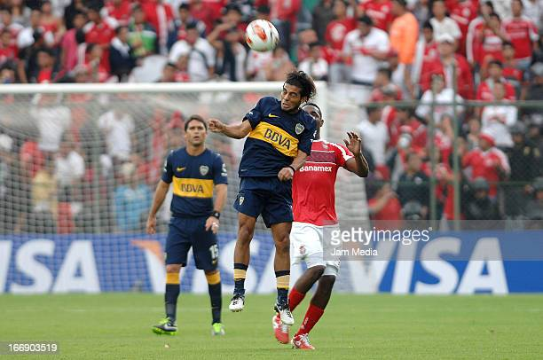 Luis Tejada of Toluca struggles for the ball with Walter Erviti of Boca Juniors during the match between Toluca from Mexico and Boca Jrs from...