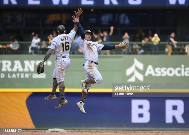 Luis Urias and Kolten Wong of the Milwaukee Brewers celebrate the team win against the Atlanta Braves at American Family Field on May 16, 2021 in...