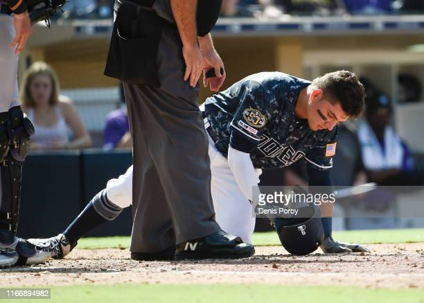 Luis Urias of the San Diego Padres is knocked down after being hit with a pitch during the sixth inning of a baseball game against the Colorado...