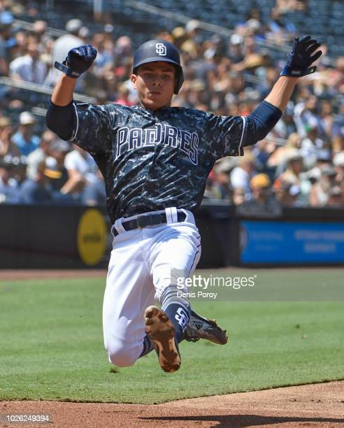 Luis Urias of the San Diego Padres slides as he scores during the first inning of a baseball game against the Colorado Rockies at PETCO Park on...