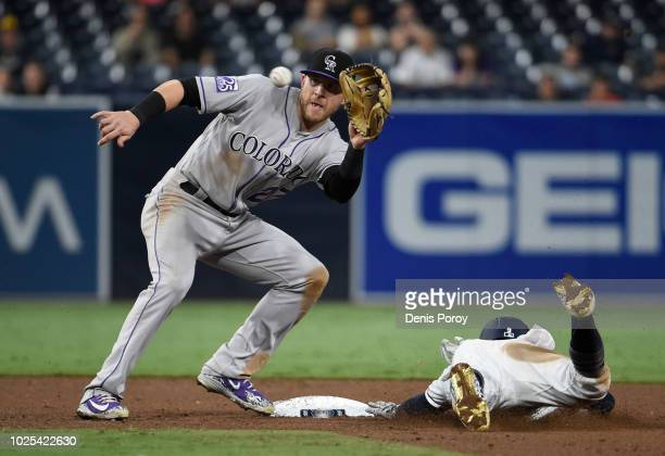 Luis Urias of the San Diego Padres steals second base ahead of the throw to Trevor Story of the Colorado Rockies in the ninth inning at PETCO Park on...