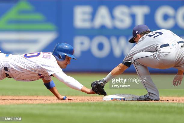 Luis Urias of the San Diego Padres tags out Michael Conforto of the New York Mets at second base during the game between the San Diego Padres and the...