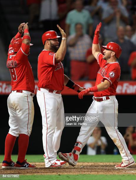 Luis Valbuena and Albert Pujols congratulate Cliff Pennington of the Los Angeles Angels at homeplate after he hit a grandslam homerun during the...