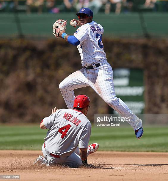 Luis Valbuena of the Chicago Cubs leaps over Yadier Molina of the St Louis Cardinals to turn a double play in the 4th inning at Wrigley Field on May...