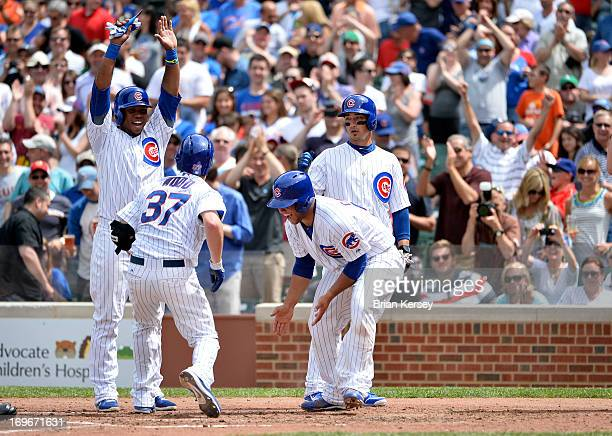 Luis Valbuena of the Chicago Cubs Welington Castillo and Darwin Barney congratulate Travis Wood at home plate after he hit a grand slam scoring the...