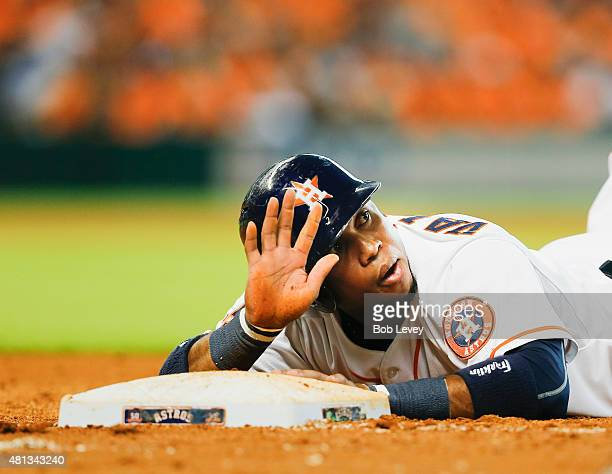 Luis Valbuena of the Houston Astros calls for timeout after diving back into first base at Minute Maid Park on July 19 2015 in Houston Texas