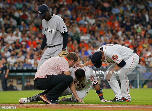 Luis Valbuena of the Houston Astros is looked at by manager AJ Hinch of the Houston Astros right and head trainer Jeremiah Randall as Didi Gregorius...