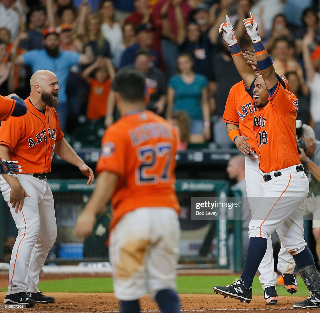 Luis Valbuena #18 of the Houston Astros is mobbed by his teammates after hitting a three run walkoff home run in the ninth inning to defeat the Oakland Athletics 10-9 at Minute Maid Park on July 8, 2016 in Houston, Texas.