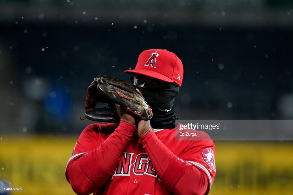 Luis Valbuena #18 of the Los Angeles Angels of Anaheim blows into his glove as he tries to stay warm in the seventh inning during a game Kansas City Royals at Kauffman Stadium on April 14, 2018 in Kansas City, Missouri.