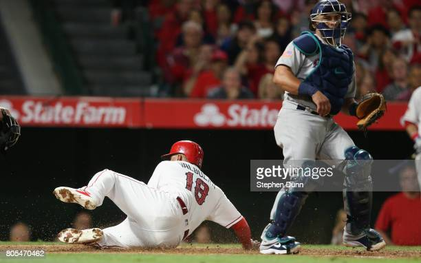 Luis Valbuena of the Los Angeles Angels of Anaheim slides past catcher Carlos Ruiz of the Seattle Mariners to score on a ground out in the seventh...