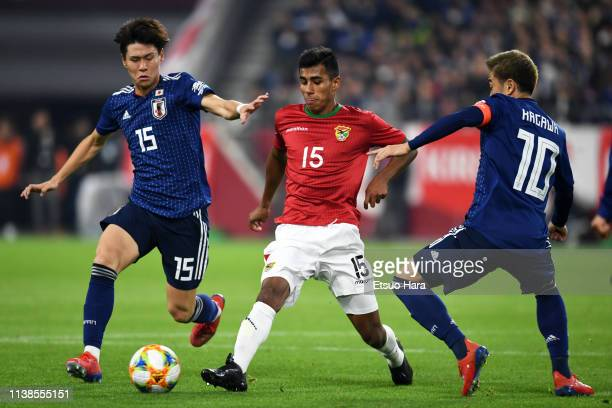 Luis Vargas of Bolivia controls the ball under pressure of Kento Hashimoto and Shinji Kagawa of Japan during the international friendly match between...