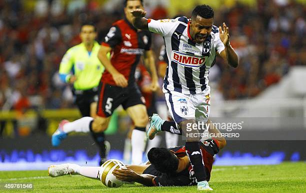 Luis Venegas of Atlas vies for the ball with Dorlan Pavon of Monterrey during a 2014 Mexican Apertura tournament football match in Guadalajara Mexico...