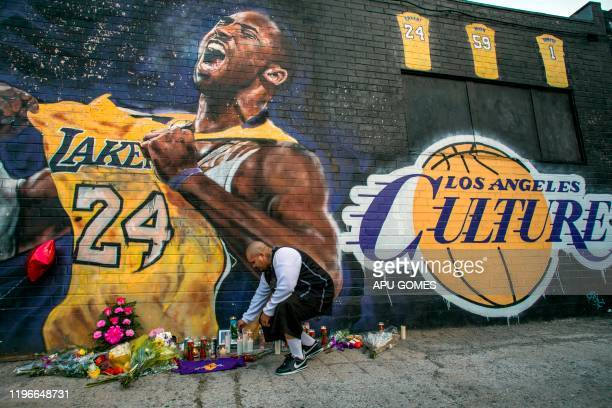 TOPSHOT Luis Villanueva lights a candle in front of a Kobe Bryant mural in downtown Los Angeles on January 26 2020 Nine people were killed in the...