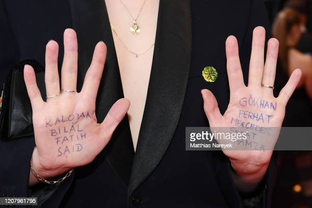 LuisaCeline Gaffron displays the names of victims of the Hanau shooting at the Persian Lesson premiere during the 70th Berlinale International Film...