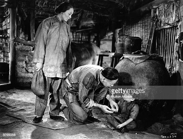 Luise Rainer and Marcella Wong star with Paul Muni in a scene from the film 'The Good Earth'