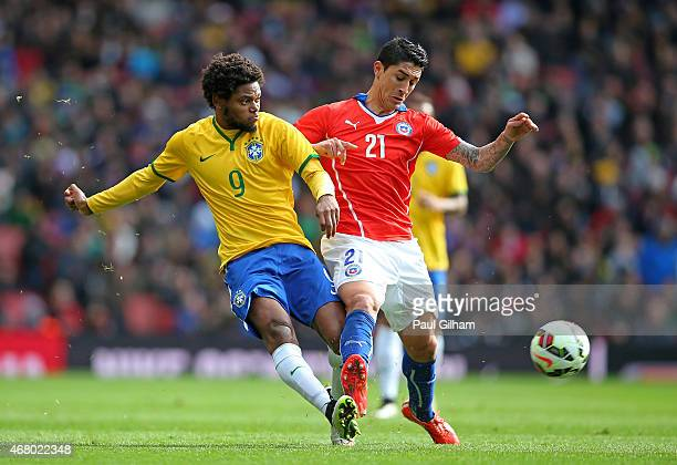Luiz Adriano of Brazil is challenged by Pablo Hernandez of Chile during the international friendly match between Brazil and Chile at the Emirates...