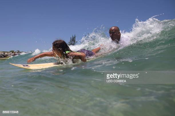 Luiz Augusto de Matos one of the teachers at Saquarema Surf School helps his pupil Luana Felix to take a wave during a class in Saquarema Rio de...