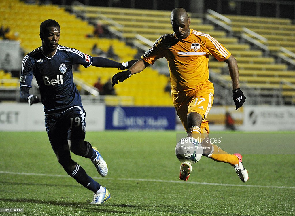 Luiz Camargo #17 of the Houston Dynamo dribbles the ball past Carlyle Mitchell #19 of the Vancouver Whitecaps FC during the second half of a game on February 20, 2013 in Charleston, North Carolina.