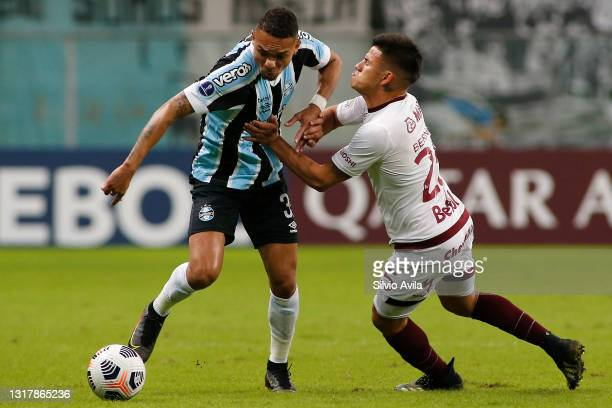 Luiz Fernando of Gremio competes for the ball with Alexander Bernabei of Lanus during a match between Gremio and Lanus as part of group H of Copa...