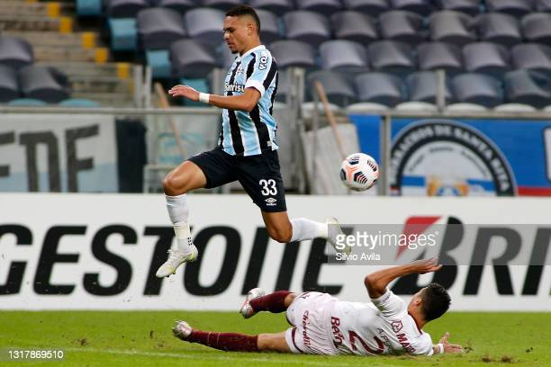 Luiz Fernando of Gremio competes for the ball with Alexis Pérez of Lanus during a match between Gremio and Lanus as part of group H of Copa CONMEBOL...