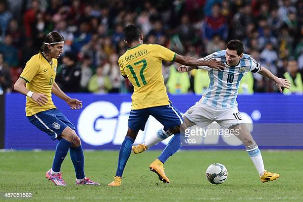 Luiz Gustavo of Brazil and Lionel Messi of Argentina battle for the ball during a match between Argentina and Brazil as part of 2014 Super Clasico at...