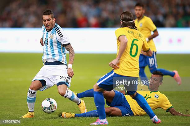 Luiz Gustavo of Brazil competes the ball with Pereyra of Argentina during Super Clasico de las Americas between Argentina and Brazil at Beijing...