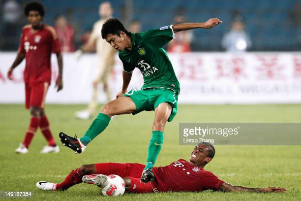 Luiz Gustavo of FC Bayern Muenchen challenges with Li Tixiang of Beijing Guoan during the preseason friendly match between Beijing Guo'an and Bayern...