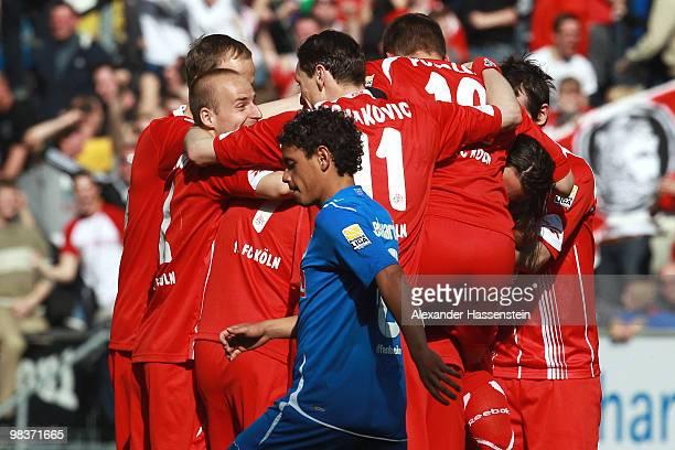 Luiz Gustavo of Hoffenheim looks dejected whilst players of Koeln celebrate their first team goal during the Bundesliga match between 1899 Hoffenheim...