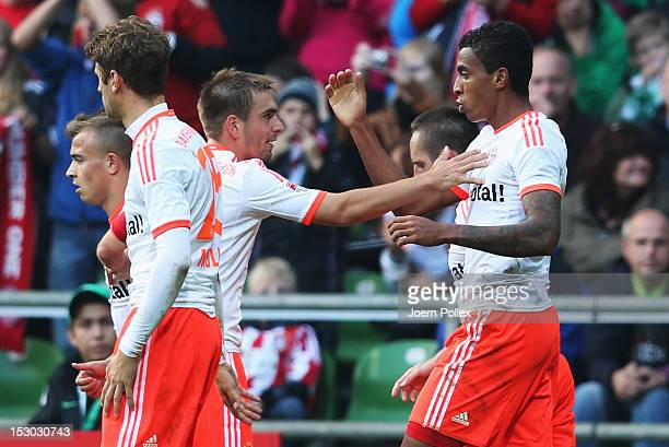 Luiz Gustavo of Muenchen celebrates with his team mate Philipp Lahm after scoring his team's first goal during the Bundesliga match between SV Werder...