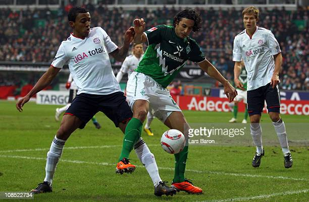 Luiz Gustavo of Muenchen challenges Claudio Pizarro of Bremen during the Bundesliga match between SV Werder Bremen and FC Bayern Muenchen at Weser...