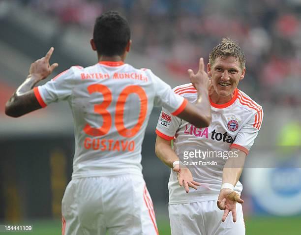 Luiz Gustavo of Munich celebrates scoring his goal with Bastian Schweinstieger during the Bundesliga match between Fortuna Duesseldorf 1895 and FC...