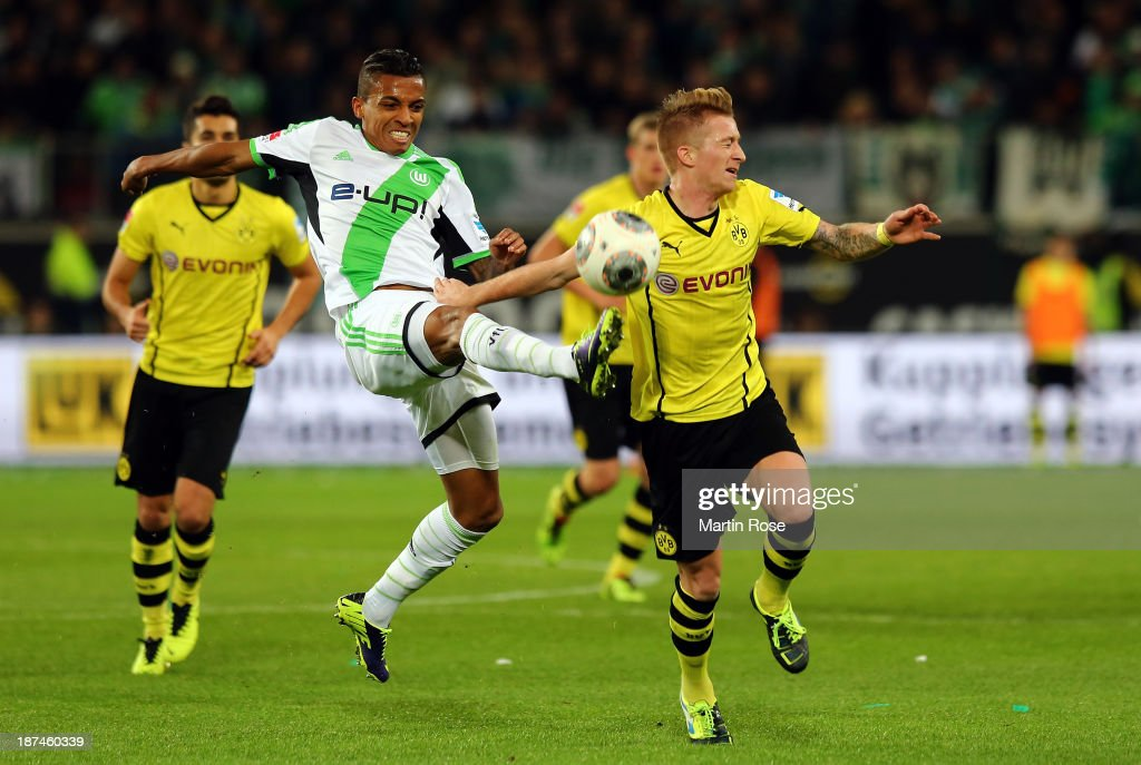 Luiz Gustavo (L) of Wolfsburg and Marco Reus (R) of Dortmund battle for the ball during the Bundesliga match between VfL Wolfsburg and Borussia Dortmund at Volkswagen Arena on November 9, 2013 in Wolfsburg, Germany.