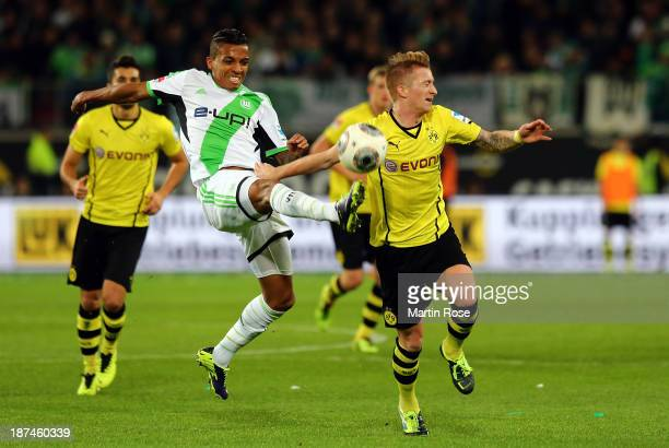 Luiz Gustavo of Wolfsburg and Marco Reus of Dortmund battle for the ball during the Bundesliga match between VfL Wolfsburg and Borussia Dortmund at...