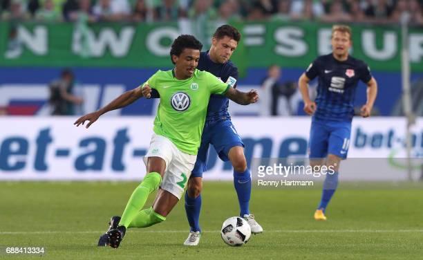 Luiz Gustavo of Wolfsburg competes with Mirko Boland of Braunschweig during the Bundesliga Playoff first leg match between VfL Wolfsburg and...