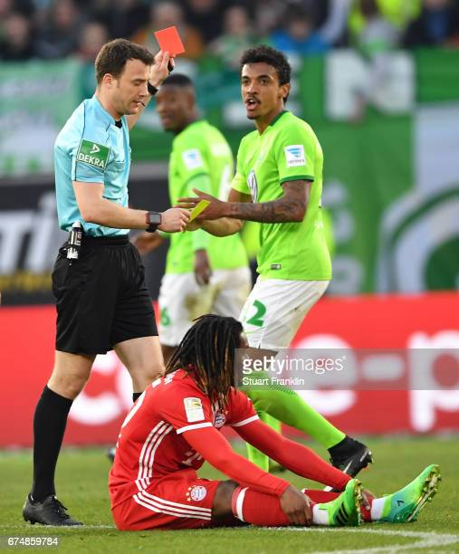 Luiz Gustavo of Wolfsburg is shown the red card by the referee during the Bundesliga match between VfL Wolfsburg and Bayern Muenchen at Volkswagen...