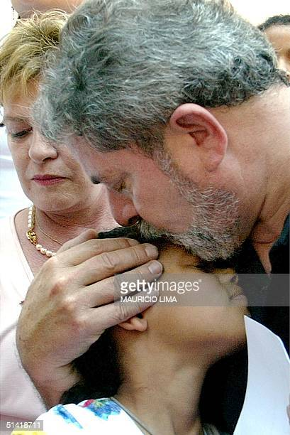 Luiz Inacio Lula da Silva Brazilian presidential candidate for the Workers Party kisses a girl while Lula's wife Marisa stands behind 08 October 2002...