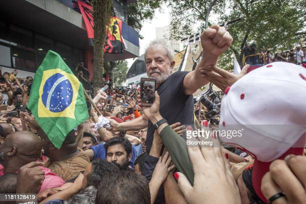 Luiz Inacio Lula da Silva Brazil's former president center holds a Brazilian flag while being carried by supporters after speaking at a rally in...