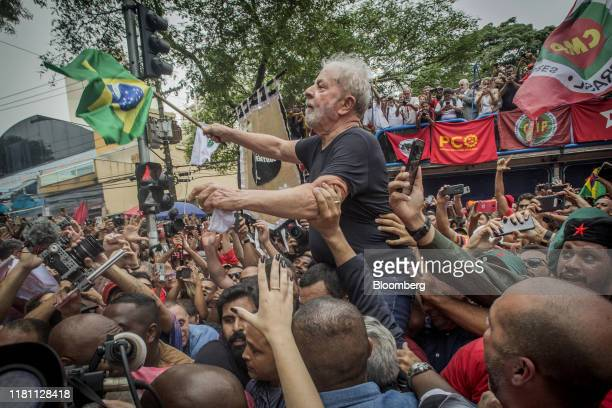 Luiz Inacio Lula da Silva Brazil's former president center waves a Brazilian flag while being carried by supporters after speaking at a rally in...