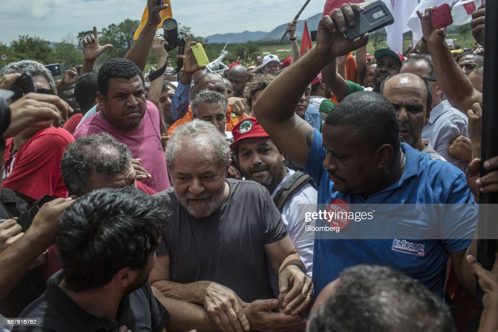 Luiz Inacio Lula da Silva, former president of Brazil, center, greets supporters during a presidential pre-campaign rally outside the Petroleo Brasileiro SA (Petrobras) Petrochemical Complex in Itaborai, Brazil, on Thursday, Dec. 7, 2017. Brazil's 2018 presidential race is shaping up to be an inflection point in the nation's three-decade-old democracy. While markets are hoping for a centrist, reformist candidate, polls show Lula leading despite a conviction on corruption charges that may bar him from running. Photographer: Dado Galdieri/Bloomberg via Getty Images