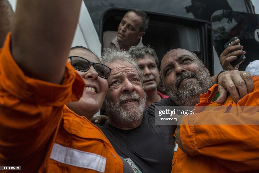 Luiz Inacio Lula da Silva, former president of Brazil, center, takes a selfie photograph with supporters during a presidential pre-campaign rally outside the Petroleo Brasileiro SA (Petrobras) Petrochemical Complex in Itaborai, Brazil, on Thursday, Dec. 7, 2017. Brazil's 2018 presidential race is shaping up to be an inflection point in the nation's three-decade-old democracy. While markets are hoping for a centrist, reformist candidate, polls show Lula leading despite a conviction on corruption charges that may bar him from running. Photographer: Dado Galdieri/Bloomberg via Getty Images