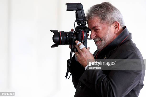 Luiz Inacio Lula da Silva president of Brazil uses a photojournalist's camera before meeting with Jacob Zuma president of South Africa at the...