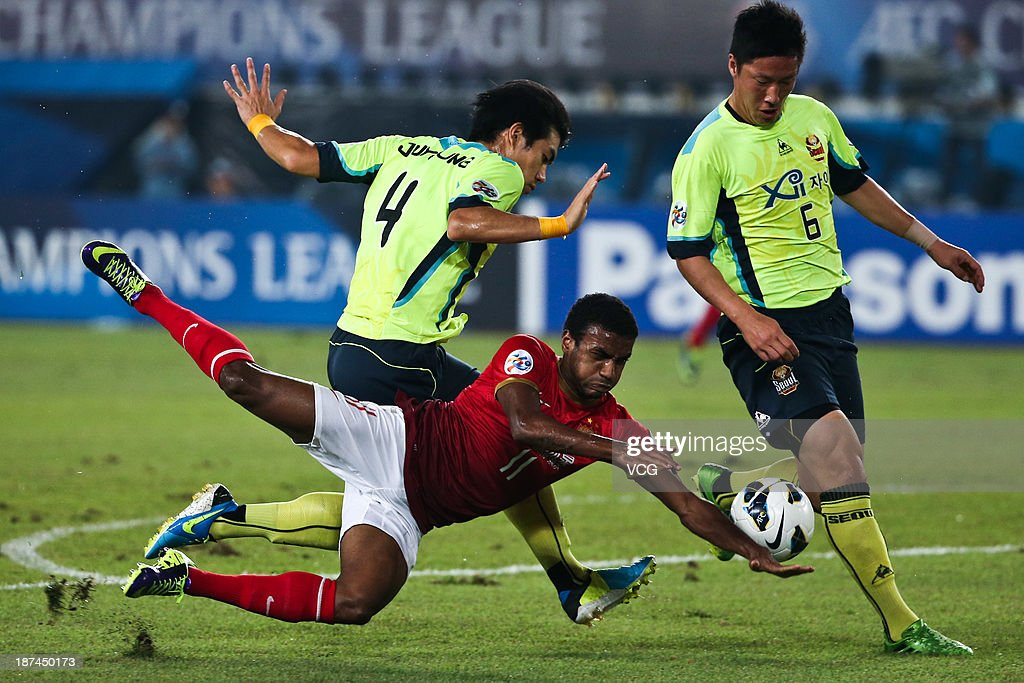 Luiz Muriqui of Guangzhou Evergrande is challenged by Kim Ju-Young (L) and Kim Jin-Kyu (R) of FC Seoul during the AFC Champions League Final 2nd leg match between Guangzhou Evergrande and FC Seoul at Tianhe Sports Center on November 9, 2013 in Guangzhou, China.
