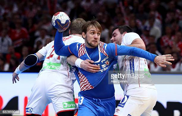 Luka Cindric of Croatia challenges Magnus Gullerud and Goran Johannessen of Norway during the 25th IHF Men's World Championship 2017 Semi Final match...