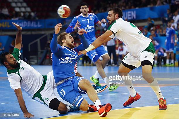 Luka Cindric of Croatia is challenged by Hassan Aljanabi and Mahdi Alsalem of Saudi Arabia during the 25th IHF Men's World Championship 2017 match...