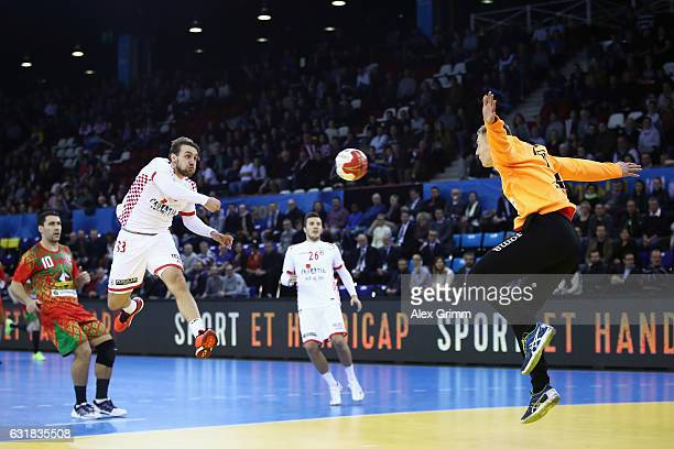 Luka Cindric of Croatia scores a goal against goalkeeper Viachaslau Saldatsenka of Belarus during the 25th IHF Men's World Championship 2017 match...