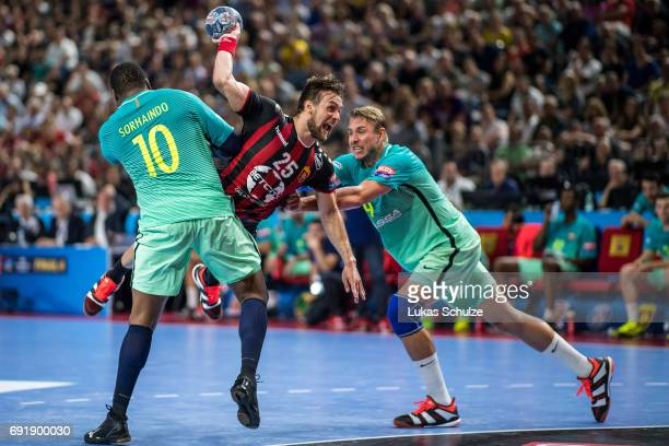 Luka Cindric of Vardar is attacked by Cedric Sorhaindo and Filip Jicha of Barcelona during the VELUX EHF FINAL4 Semi Final match between HC Vardar...