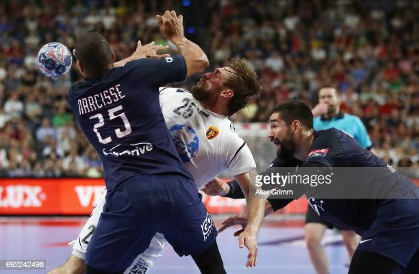 Luka Cindric of Vardar is challenged by Daniel Narcisse and Nikola Karabatic of Paris during the VELUX EHF FINAL4 final between Paris SaintGermain...