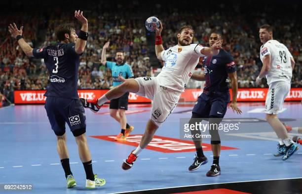 Luka Cindric of Vardar is challenged by Uwe Gensheimer and Daniel Narcisse of Paris during the VELUX EHF FINAL4 final between Paris SaintGermain...